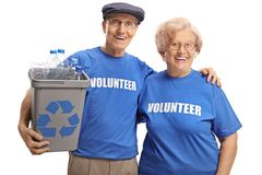 Senior volunteers with a recycle bin for plastic bottles. Isolated on white background royalty free stock photography