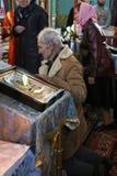 Senior. VOYUTYN, UKRAINE - 14 October 2008: Uktainian parishioners of the Orthodox Church light up candles during the religious celebration Pokrov Stock Image