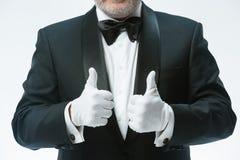 Senior waiter in white gloves stock image
