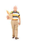 Senior walking with a bag of groceries Stock Images