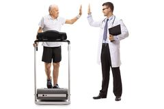 Senior walking on a treadmill and high-fiving a doctor Royalty Free Stock Images
