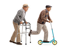 Senior walking with a walker and another senior riding a scooter. Full length profile shot of a senior walking with a walker and another senior riding a scooter Royalty Free Stock Images