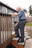 Senior walks up wooden deck steps outside. Senior man walks up the wooden deck steps in the backyard, with one hand on the rail royalty free stock image