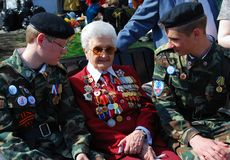 Senior war veteran and two young military men Stock Image