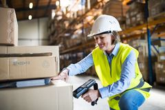 Senior warehouse woman worker working with barcode scanner. Senior warehouse woman worker or supervisor using a mobile handheld PC with barcode scanner royalty free stock image