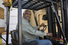 Senior Warehouse Worker Driving Forklift. Portrait of a happy senior warehouse worker driving forklift Royalty Free Stock Photos