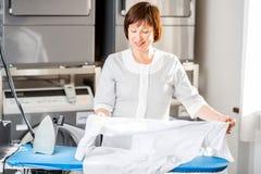 Senior washwoman ironing in the laundry Stock Image
