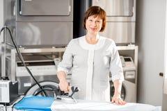 Senior washwoman ironing in the laundry Royalty Free Stock Photos