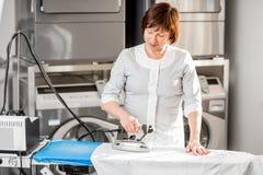 Senior washwoman ironing in the laundry Royalty Free Stock Images