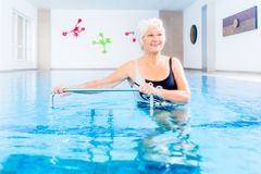 Senior in water gymnastics therapy. Senior woman in underwater gymnastics therapy with sliding machine Royalty Free Stock Images