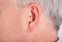 Senior wearing CIC hearing aid royalty free stock photo