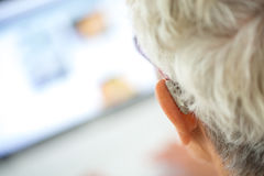 Senior wearing hearing aid in her ears in front a laptop stock photo