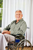 Senior in wheelchair in nursing. Smiling senior sitting in a wheelchair in a nursing home Stock Photos