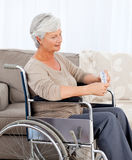 Senior in wheelchair with pills. Senior in wheelchair with weekly pills Stock Photo
