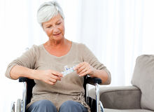 Senior in wheelchair with pills Stock Photography