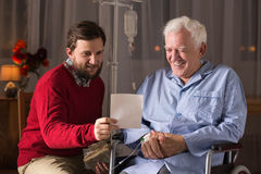 Senior on wheelchair with son Royalty Free Stock Image