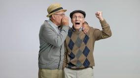 Senior whispering something funny to another senior stock video