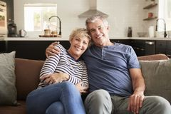 Senior white couple relaxing at home smiling to camera stock photography