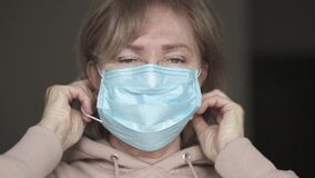 Senior white woman putting medical mask on her face
