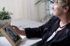 Senior widow reminiscing her husband Stock Image