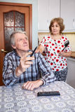 Senior wife asking lazy husband to escape from watching TV in the kitchen, mature couple relationship Royalty Free Stock Images