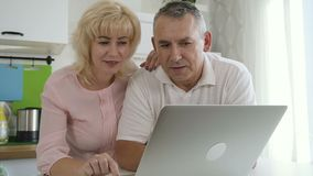 Senior wife giving advice to male pensioner during online shopping. stock video