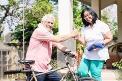 Senior wife giving a bottle of water to her husband after cycling. Careful senior wife giving a bottle of still water and a towel to her husband after cycling Royalty Free Stock Photos