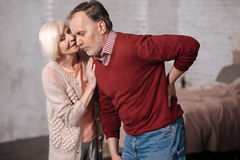 Senior wife giving solace to her husband with backache Royalty Free Stock Photography