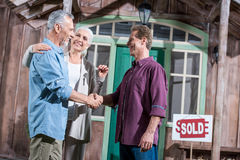 Senior wife holding keys of new house while her husband shaking hands with saleman Stock Images