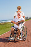 Senior wife and husband. Happy  caring senior wife pushing husband on wheelchair at beach Stock Photography