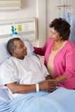 Senior Wife Visiting Husband On Ward Royalty Free Stock Images
