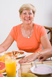 Senior woman. At breakfast table Stock Photography