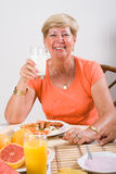 Senior woman. Drinking milk at breakfast table Royalty Free Stock Images