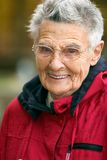 Senior woman. Smiling senior woman in red jacket with short hair wearing glasses against a blurry background. Narrow DOF with focus on the eyes Stock Image