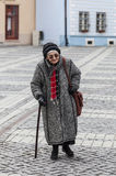 Senior woman. Image of a lonely senior woman walking in a paved city square Stock Image