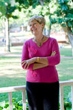 Senior woman. A happy senior woman in pink pose in the park Stock Photo