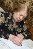 Senior woman. The elderly woman writes the letter Royalty Free Stock Photography