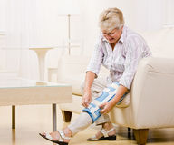 Senior woman adjusting knee brace Royalty Free Stock Photos