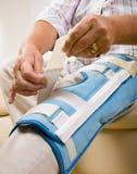 Senior woman adjusting knee brace Royalty Free Stock Images