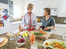 Senior woman and adult daughter cutting fresh vegetables on chopping board in kitchen, smiling Royalty Free Stock Photo