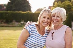 Senior woman and adult daughter embracing in garden stock photos