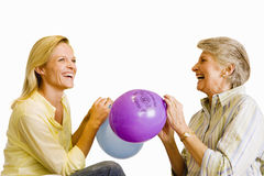 Senior woman and adult daughter inflating balloons, laughing, side view, cut out Royalty Free Stock Photography