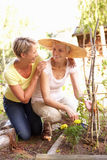 Senior Woman And Adult Daughter Relaxing In Garden Stock Photo