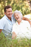 Senior Woman With Adult Son In Garden Royalty Free Stock Photography