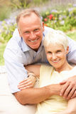Senior Woman And Adult Son Relaxing In Garden Stock Image
