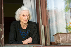 Senior woman alone on house window Royalty Free Stock Images