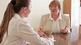 Senior woman answer questions of social worker at home
