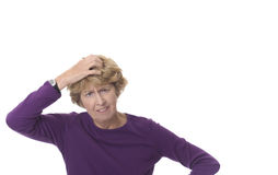 Senior woman with anxious expression. Senior woman on white background scratching her head, unable to solve a problem Royalty Free Stock Image