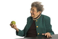 Senior woman with apple Stock Images