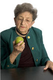 Senior woman with apple. Attractive senior woman about to eat granny smith apple business executive with pearls stock photography